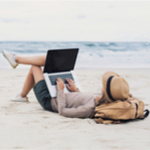 Woman on her laptop at the beach